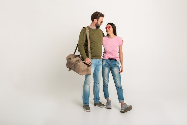 Stijlvol paar geïsoleerde, vrij lachende vrouw in roze t-shirt en man in sweatshirt met reistas, gekleed in spijkerbroek, zonnebril dragen, samen plezier hebben