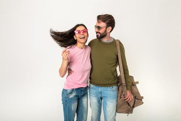 Stijlvol paar geïsoleerde, vrij lachende vrouw met lang haar in roze t-shirt en man in sweatshirt met reistas, gekleed in spijkerbroek, zonnebril dragen, samen plezier hebben