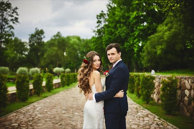 Stijlvol paar gelukkige pasgetrouwden poseren in het park na de huwelijksceremonie op hun trouwdag. perfect paar, bruid en bruidegom poseren buitenshuis