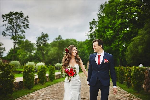 Stijlvol paar gelukkige pasgetrouwden wandelen in het park na de huwelijksceremonie op hun trouwdag. perfect paar liefhebbers, bruid en bruidegom poseren buitenshuis
