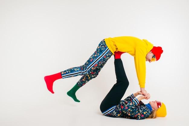 Stijlvol paar man en vrouw in kleurrijke kleding die zich voordeed op witte muur