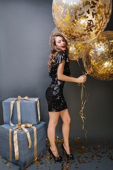 Stijlvol partijbeeld van aantrekkelijke vrolijke jonge vrouw in zwarte luxe jurk met grote ballonnen vol met gouden tinsels. gelukkige verjaardag, cadeautjes, vieringen, echte emoties.