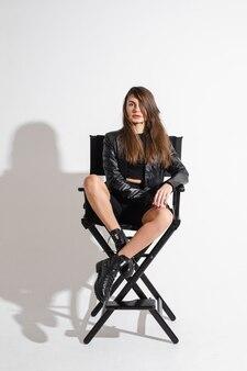 Stijlvol passen modern jong vrouwelijk model met gezonde lange haren in zwarte eigentijdse kleding, zittend in een stoel in de studio.