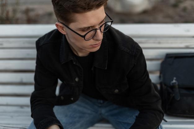 Stijlvol portret jongeman model met trendy kapsel in modieuze denim zwarte jas in vintage bril met leren rugzak op straat in de stad. aantrekkelijke man zit op een houten bankje.