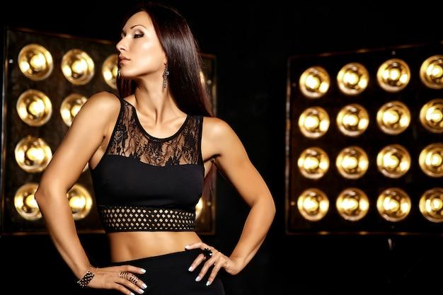 Stijlvol portret van een mooi meisjesmodel in zwarte kleren die op de zwarte achtergrond van studiolichten stellen
