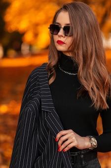 Stijlvol portret van een mooie jonge vrouw met rode lippen in mode kleding met een zwarte trui en een blazer met zonnebril buiten in een herfstpark met oranje herfstbladeren
