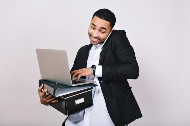 Stijlvol portret vrolijke drukke knappe man in wit overhemd en zwarte jas met mappen, laptop, praten over de telefoon. zakenman, groot succes, glimlachen, bezig zijn, bezetting.