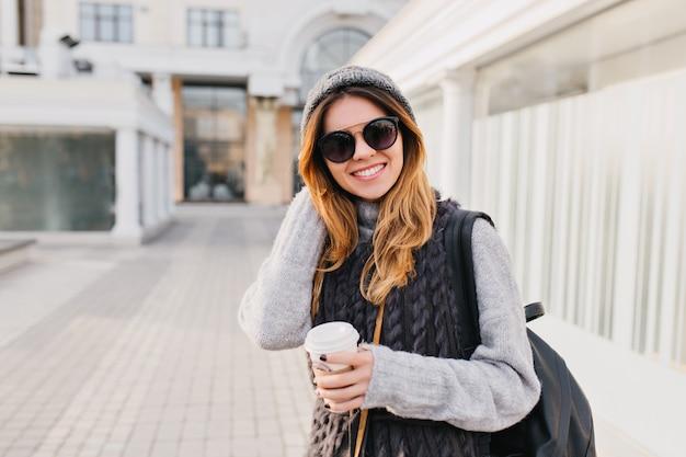 Stijlvol portret vrolijke modieuze vrouw met lang blond haar, gebreide muts, warme wollen trui en moderne zonnebril wandelen in het stadscentrum. reizen met koffie om te gaan, geluk. plaats voor tekst.