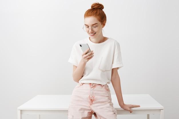 Stijlvol roodharig meisje dat pauze heeft, die tevreden mobiele telefoon bekijkt