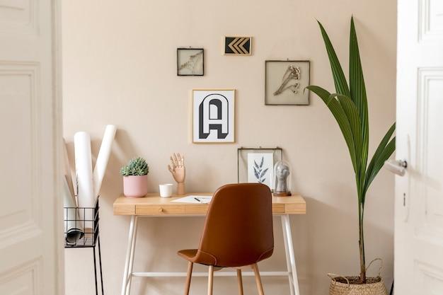 Stijlvol scandinavisch interieur van thuiskantoorruimte met veel fotolijsten, houten bureau, bruine stoel, planten, kantoor en persoonlijke accessoires. moderne neutrale huisstaging.