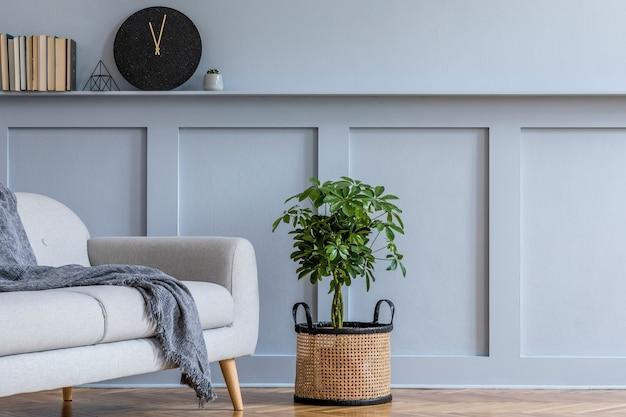 Stijlvol scandinavisch interieur van woonkamer met grijze bank, kussens, boeken, zwarte klok, houten lambrisering met plank, elegante persoonlijke accessoires en planten in design modern interieur.