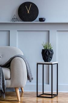 Stijlvol scandinavisch interieur van woonkamer met grijze bank, plaid, zwarte klok, houten lambrisering met plank, marmeren kruk, planten en elegante persoonlijke accessoires in design home decor.