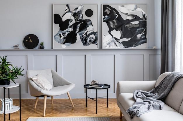 Stijlvol scandinavisch interieur van woonkamer met grijze designbank, fauteuil, marmeren kruk, zwarte salontafel, moderne schilderijen, decoratie, plant en elegante persoonlijke accessoires in woondecoratie.