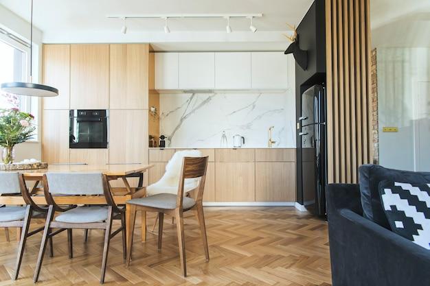 Stijlvol scandinavisch keuken- en eetkamerinterieur met familietafel en stoelen en accessoires