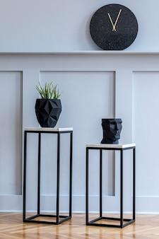Stijlvol scandinavisch woonkamerinterieur met design marmeren krukken, planten, zwarte klok op de plank en elegante accessoires in een minimalistisch interieur.