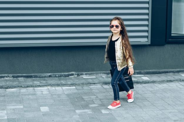 Stijlvol schattig meisje met zwarte papieren zak komt terug van winkelen
