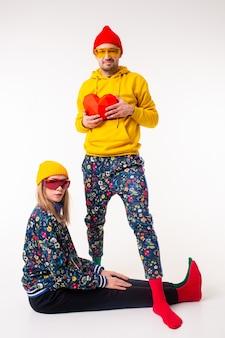 Stijlvol schattig paar man en vrouw in kleurrijke kleding poseren met hart over witte muur
