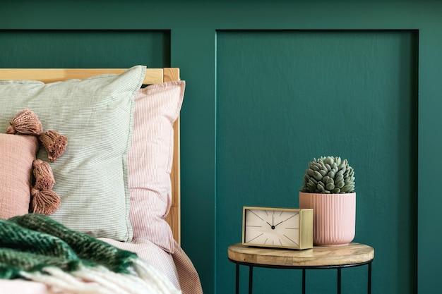 Stijlvol slaapkamerinterieur met design salontafel, plant, gouden klok en elegante persoonlijke accessoires. mooie lakens, deken en kussens. moderne huisopvoering. wandbekleding. details