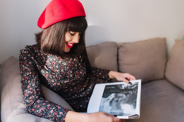 Stijlvol spectaculair meisje in rode baret kijkt met interesse naar het fotoboek, leunend met haar ellebogen op een grijze bank. portret van charmante jonge franse vrouw in vintage kleding tijdschrift lezen in vrije tijd
