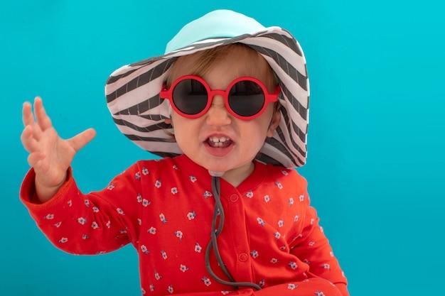 Stijlvol speels kind in zonnebril en gestreepte hoed