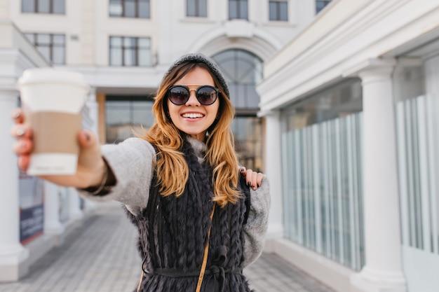 Stijlvol stadsportret van glimlachende blije jonge vrouw die koffie uitrekt om te gaan. goedemorgen van modieuze vrouw in moderne zonnebril, wollen trui, plezier buitenshuis.