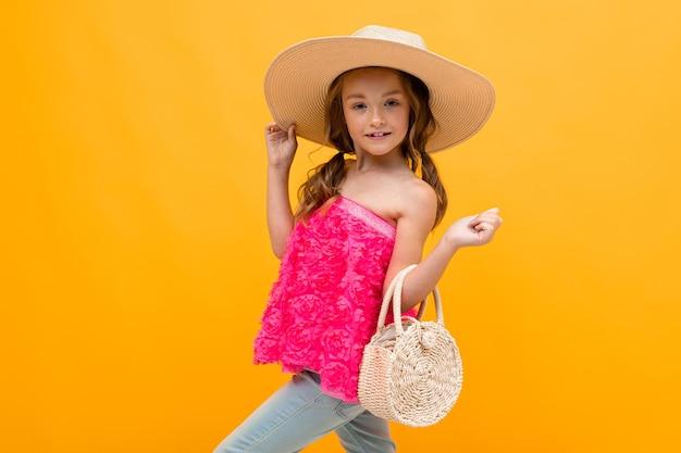 Stijlvol tienermeisje in een roze blouse met een strooien hoed op haar hoofd