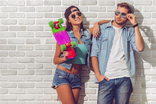 Stijlvol tienerpaar in jean kleding, petten en zonnebril