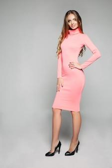 Stijlvol, verbluffend model in casual body-hugging roze jurk en hakken.