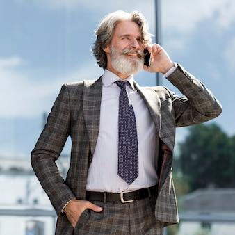 Stijlvol volwassen mannetje dat aan de telefoon spreekt