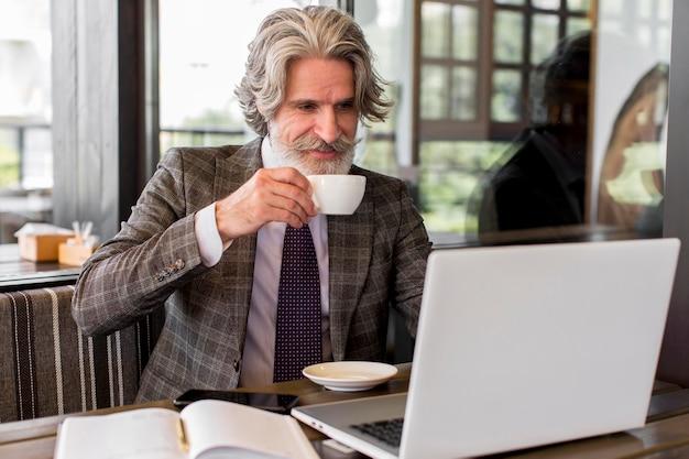Stijlvol volwassen mannetje dat van koffie geniet op kantoor