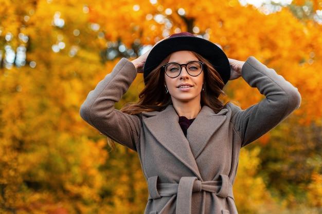 Stijlvol vrij jong vrouwenmannequin zet chique hoed recht. aantrekkelijke vrij trendy hipster meisje in elegante jas met bril vormt in herfst park. modieuze seizoenskleding voor dames. stijl.