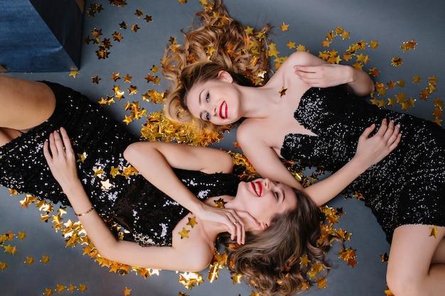 Stijlvol vrolijk feestbeeld van bovenaf twee aantrekkelijke jonge vrouwen in luxe zwarte jurken tot in gouden tinsels. plezier hebben, lachen, glimlachen, echte positieve emoties uiten.