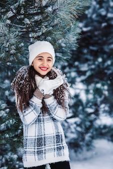 Stijlvol vrolijk meisje bezaaid met sneeuw in het winter woud