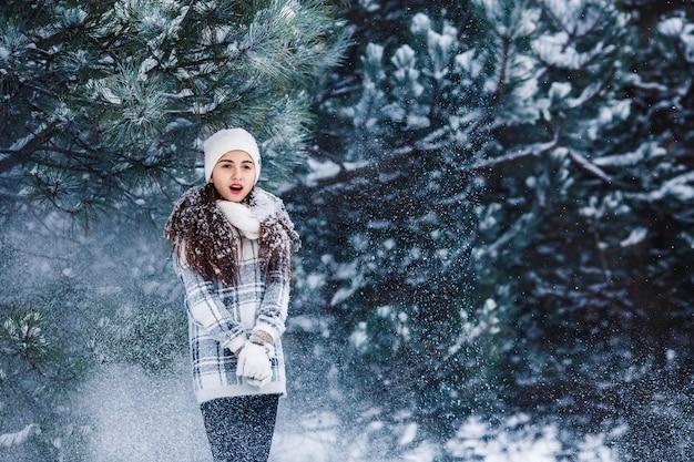 Stijlvol vrolijk meisje in een trui in het winterbos sneeuw van de boom valt op het meisje