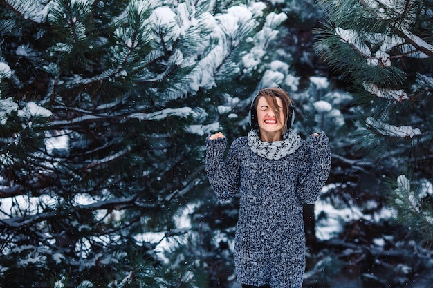 Stijlvol vrolijk meisje in een trui in het winterbos