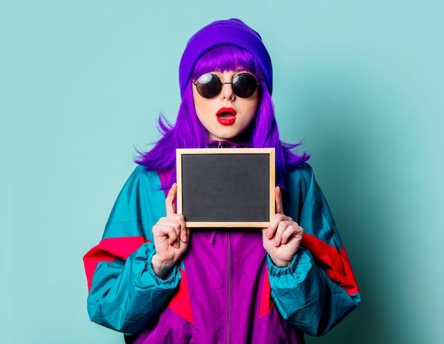Stijlvol wit meisje met paars haar en trainingspak houden bord op blauwe muur