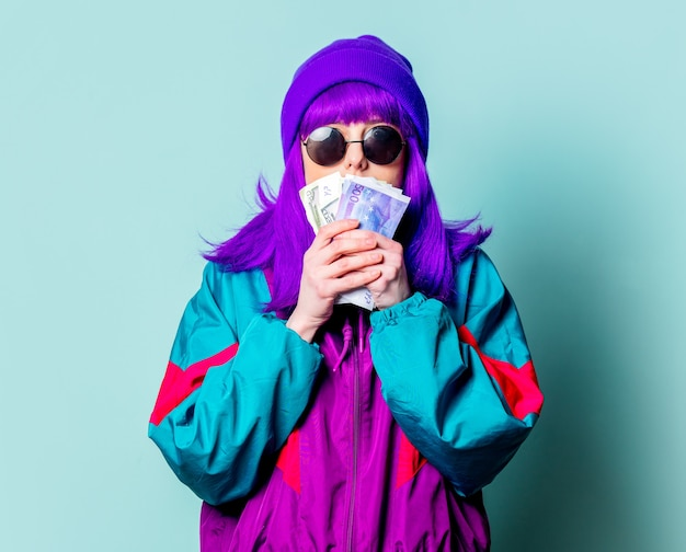 Stijlvol wit meisje met paars haar en trainingspak houdt contant geld op blauwe muur