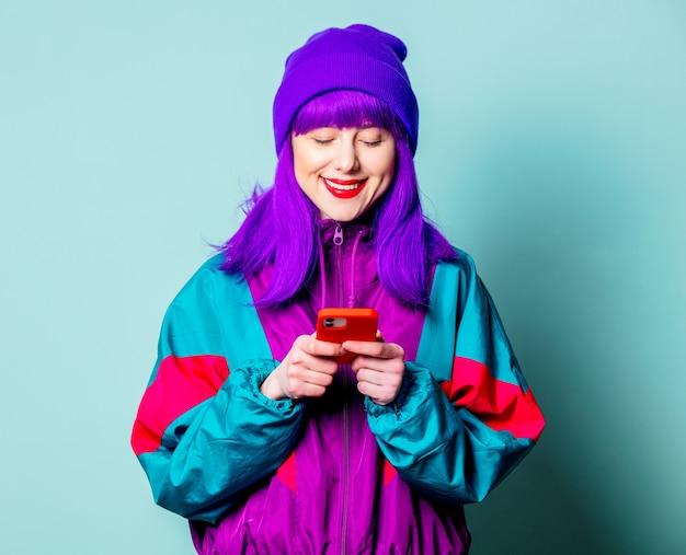 Stijlvol wit meisje met paars haar en trainingspak met behulp van mobiele telefoon op blauwe muur