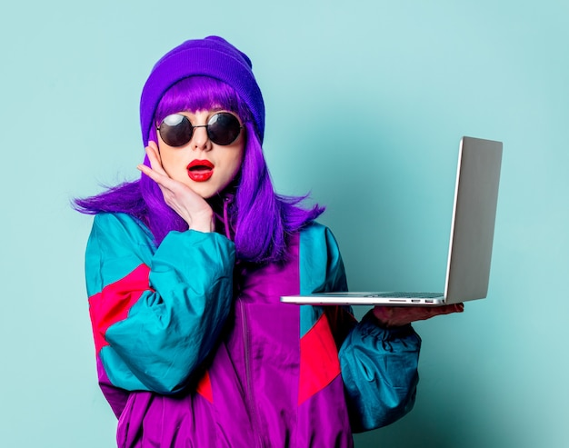 Stijlvol wit meisje met paars haar en trainingspak met laptop op blauwe muur