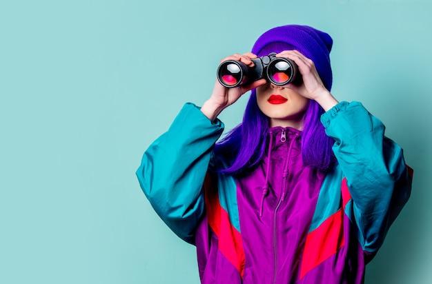 Stijlvol wit meisje met paars haar en trainingspak met verrekijker op blauwe muur