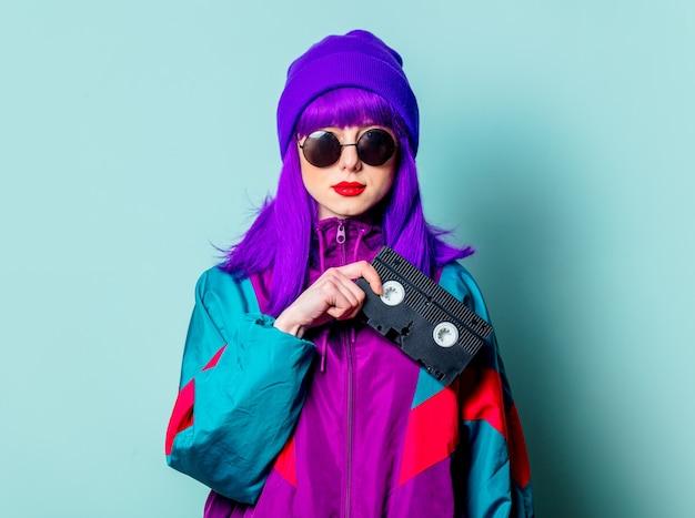 Stijlvol wit meisje met paars haar, trainingspak en zonnebril houdt videoband op blauwe muur