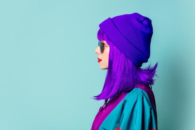 Stijlvol wit meisje met paars haar, trainingspak en zonnebril op blauwe muur. zijaanzicht