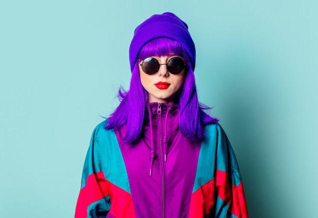 Stijlvol wit meisje met paars haar, trainingspak en zonnebril op blauwe muur