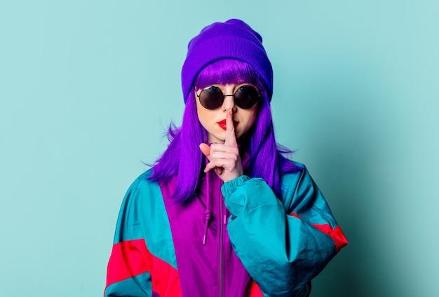 Stijlvol wit meisje met paars haar, trainingspak en zonnebril toont rustig gebaar op blauwe muur