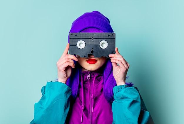 Stijlvol wit meisje met paars haar, trainingspak houdt videoband op blauwe muur