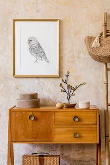 Stijlvol woonkamerinterieur met vintage commode, gouden mock-up fotolijst, houten ladder, tas, decoratie, grungemuur en elegante persoonlijke accessoires in retro interieur.