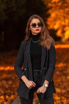 Stijlvol zakenvrouw model met vintage zonnebril in mode pak met zwarte blazer en trui buiten op herfstdag.