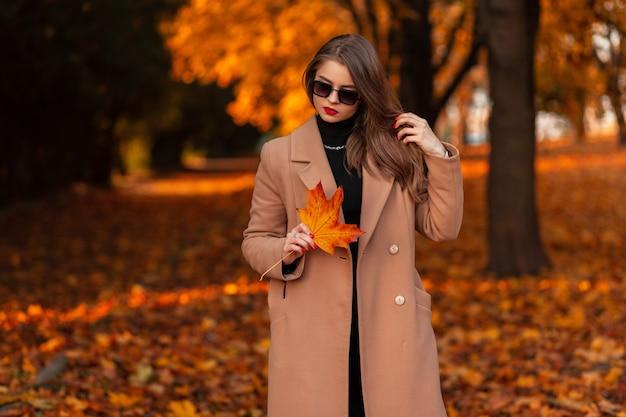 Stijlvol zakenvrouwmodel met vintage zonnebril in modieuze beige jas met oranjerood gekleurd blad loopt in het park met fel herfstgebladerte