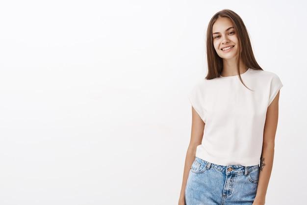 Stijlvol zelfverzekerd en aantrekkelijk volwassen vrouwelijk model met tatoeage op arm poseren in trendy witte blouse en spijkerbroek hoofd kantelen en lachend met zorgeloze vriendelijke uitstraling