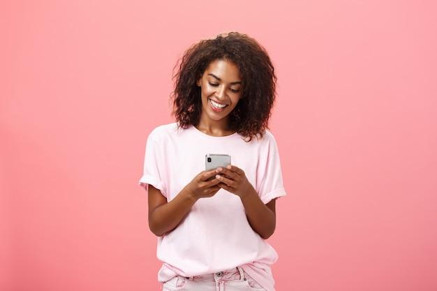 Stijlvol, zorgeloos meisje sms-vriend komt over staande blij over oranje muur in stijlvolle denim shorts bericht typen of scrollen nieuws op internet via smartphone starend naar het scherm van het apparaat met een glimlach